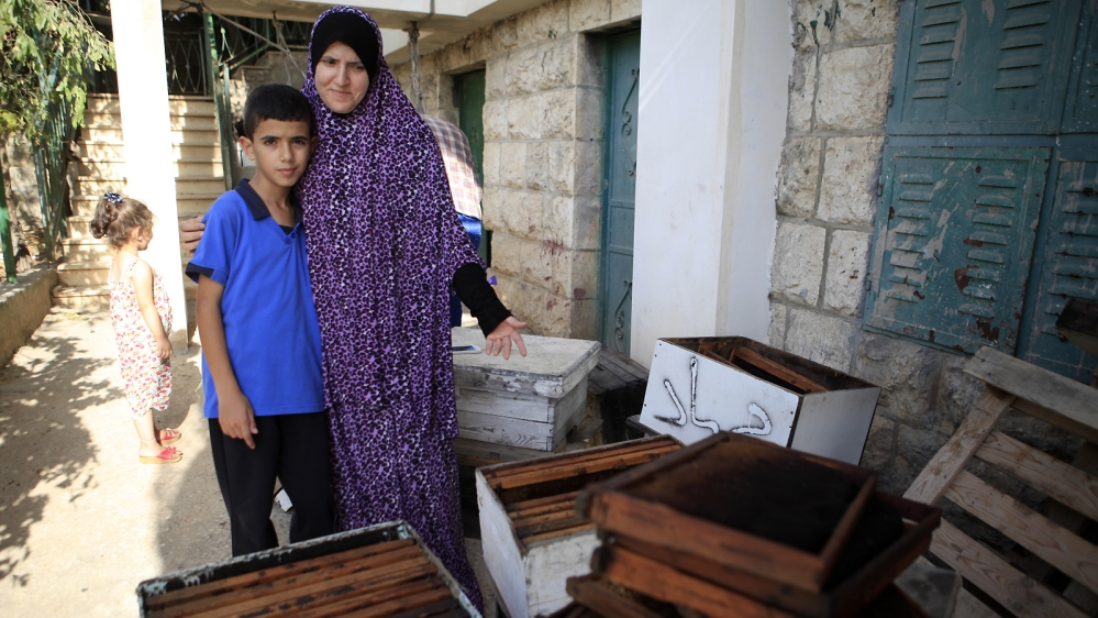 Taha shows her empty beehives: 'Last year, we had bees so we could produce our own honey, but all the bees died due to lack of water; there are not enough flowers' [Eloise Bollack/Al Jazeera]