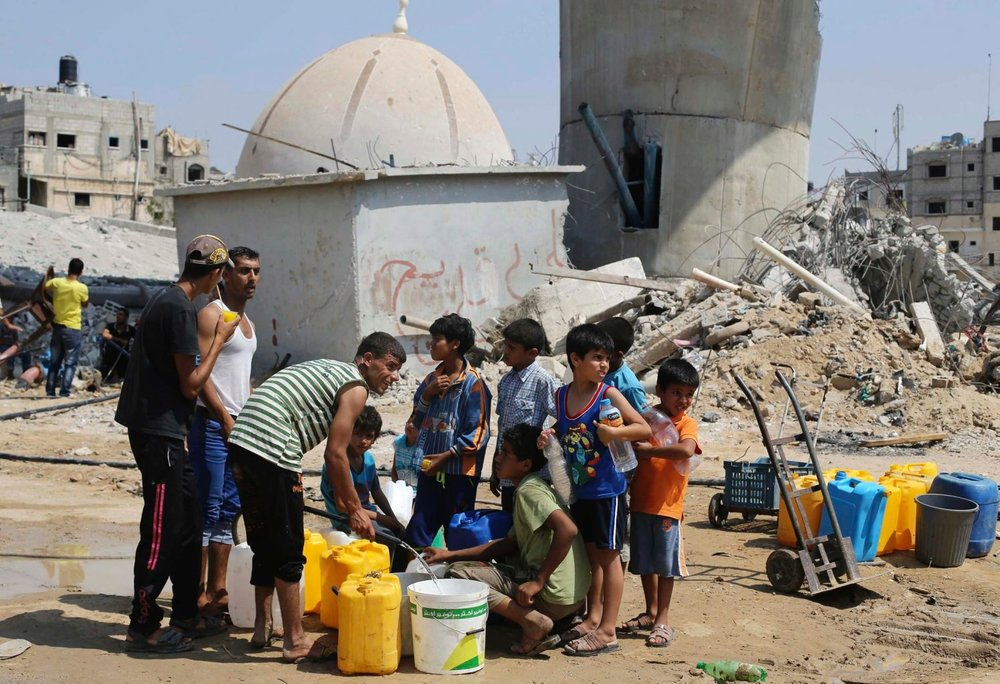 Palestinian children collect water during a five-day truce in Khan Yunis, in the southern Gaza Strip, August 14, 2014. Reuters
