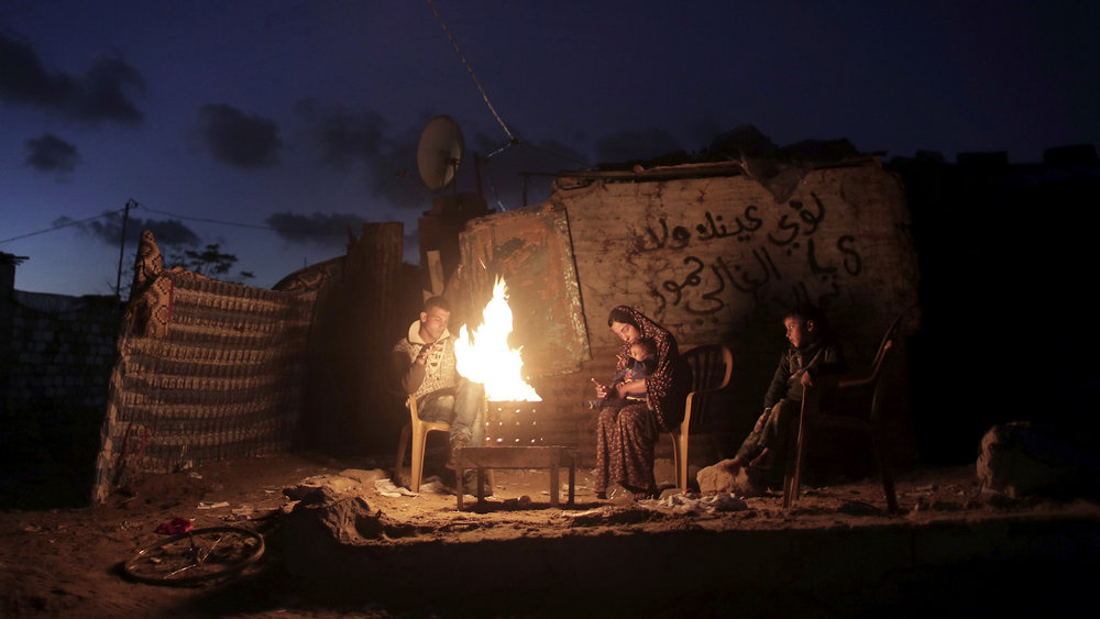 A Palestinian family warm themselves on a fire outside their makeshift home during a power cut in Khan Younis in the southern Gaza Strip. (AP/ Khalil Hamra)