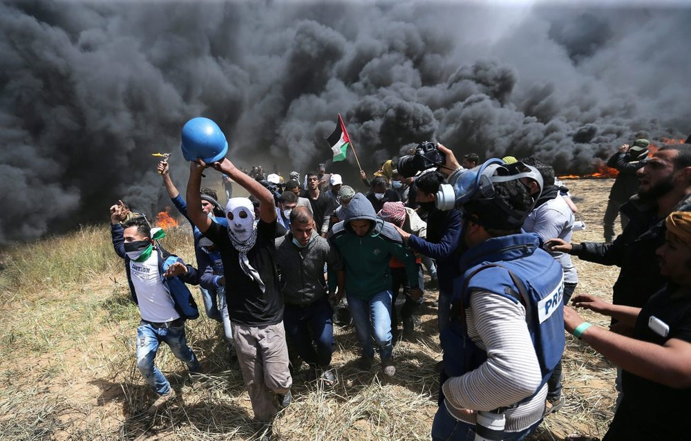Palestinians evacuate mortally wounded Palestinian journalist Yasser Murtaja, 31, during clashes with Israeli troops at the Israel-Gaza border\ IBRAHEEM ABU MUSTAFA/ REUTERS
