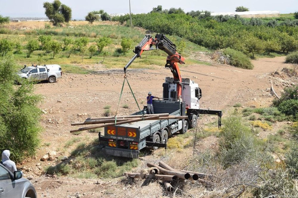 Israeli forces can be seen confiscating pipes in the Jordan Valley. (Ma'am News Agency)