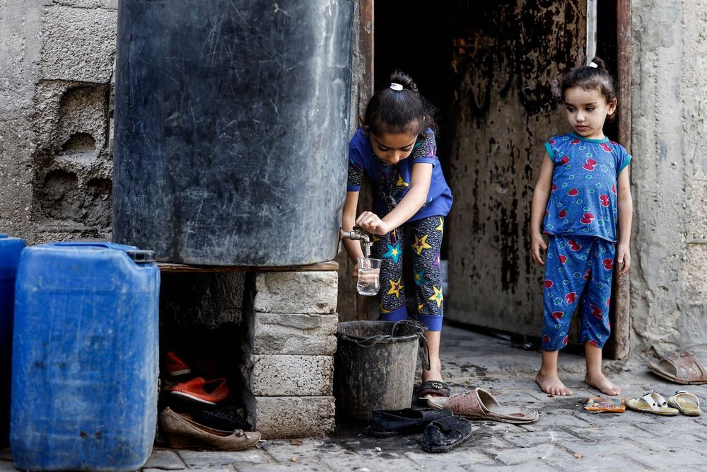 A Palestinian girl fills up a bottle with water from a cistern in the southern Gaza Strip on Oct. 24. (Thomas Coex/AFP/Getty Images)