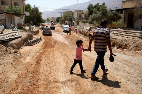 A father and his daughter cross a street under renovations as part of a U.S. aid grant in the village of al-Badhan, north of Nablus in Israeli occupied West Bank in August 2018.    JAAFAR ASHTIYEH / AFP/GETTY IMAGES