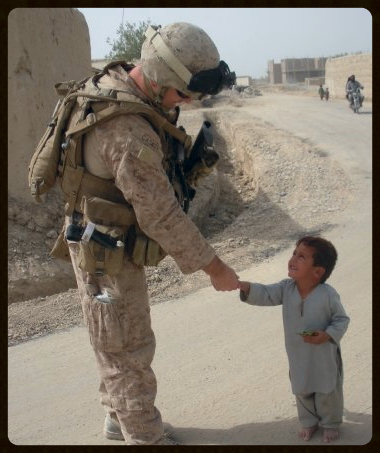 During his Third tour of duty,Caskey greets a young citizen of Afghanistan.