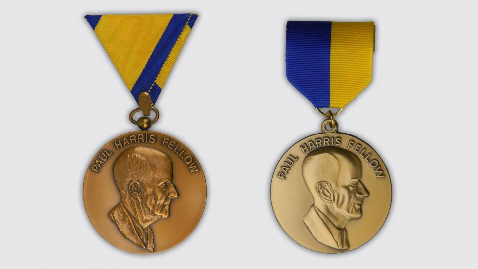 The first Paul Harris Fellow medallion (left) and a later version. Various lapel and neck ribbons were used with this medallion throughout the years.