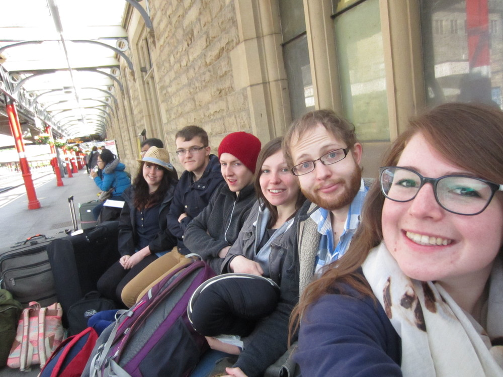 Waiting at the train station in cold, rainy UK, and looking forward to a crazy 24 hours of travel!