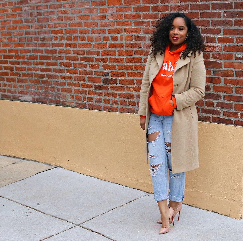Orange hoodie, nude pumps, camel coat