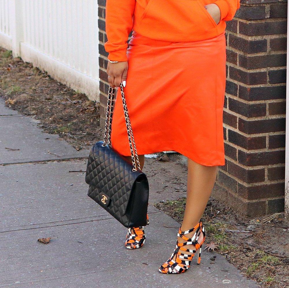 Monochromatic Look: Orange Sweatshirt, Leather Midi Skirt, Snakeskin Print Heels, Bamboo Earrings, Chanel Purse
