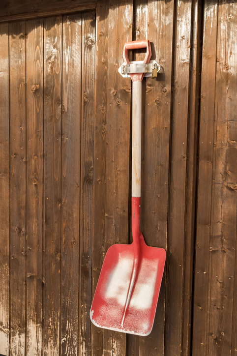 Ice and snow shovel in storage shed barn.
