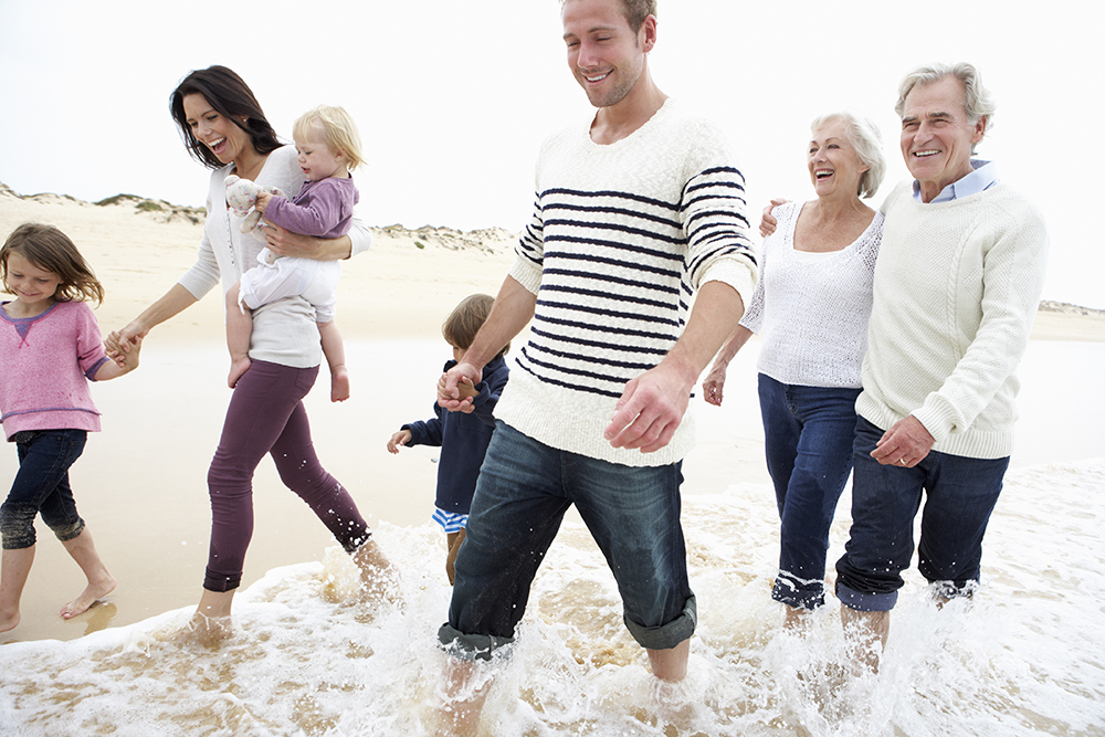 Multi-Generation-Family-Walking-Along-Beach-Together-000021765403_Full.jpg