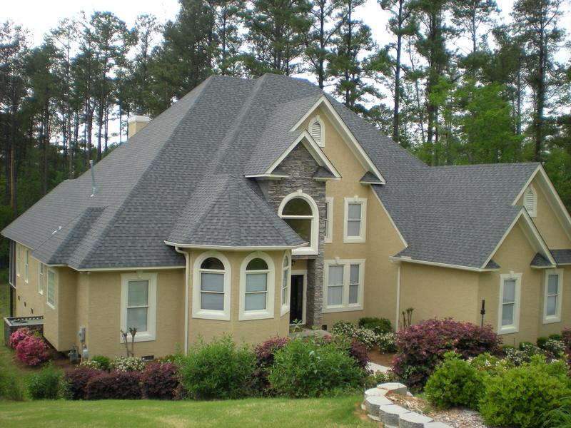 Exterior painting of a large stucco home in Evans, Georgia.