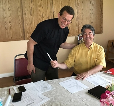 Congratulations on Finalization of the New Building Fund! -  Father Dusan Koprivica and Council President Phil Frantzis at the signing table.