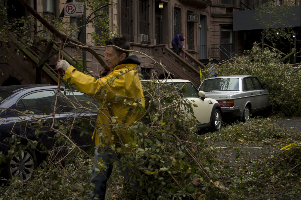 Residents remove downed trees in Manhattan.