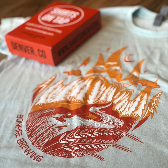 This months @bonfirebrewing shirt featuring a hand drawn design from @mtn_creative 🔥 really makes us want to get outdoors and share some beers around a fire! #bonfirebrewing #colorado #shopsmall