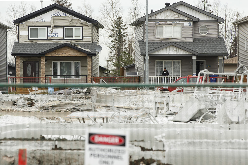 Residents go through damaged homes in Fort McMurray's Abasand neighbourhood, as a fence surrounds the remains of neighbours on Wednesday, June 8, 2016.  The neighbourhood was one of the hardest hit areas when the city was struck by wildfires. Ian Kucerak/Postmedia Network