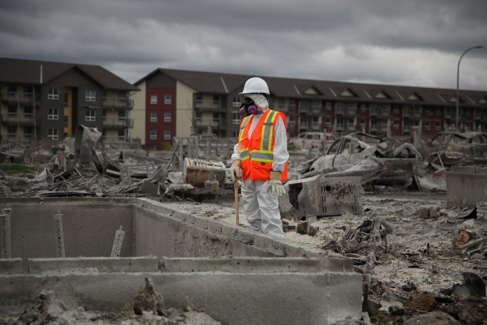 A volunteer with Team Rubicon pauses between sifting through the remains of a home on Prospect Drive on June 12, 2016. Olivia Condon/Fort McMurray Today/Postmedia Network