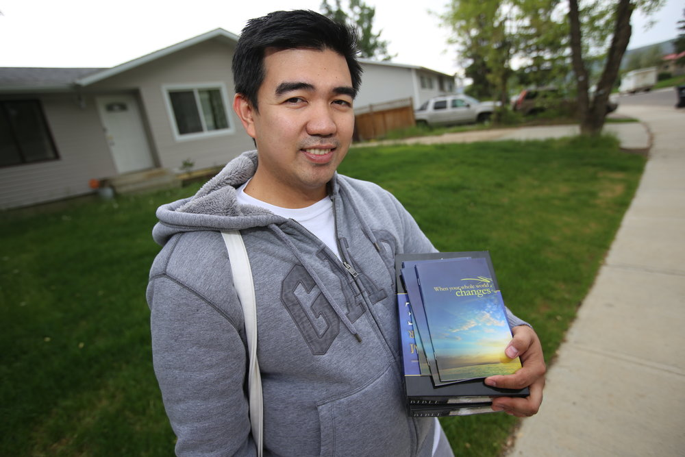 Russell   Boston , 32, poses outside his downtown  Fort   McMurray  home after surveying it for damage on June 1, 2016. The books he is holding are a bible and religious books by the American evangelist preacher Billy Graham. Vincent McDermott/ Fort   McMurray  Today/Postmedia Net  work