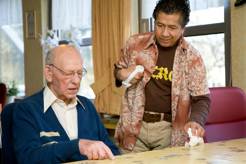 NOES TITALEY  Bij een andere woonruimte van de Meerpaal werkt de heer Noes Titaley. Drie dagen per week van 08:00 tot 12:00 uur. Hij zorgt dat de bewoners drinken krijgen met een plakje ontbijtkoek of een lekker koekje erbij. Tegen twaalven dekt hij de tafels voor de warme maaltijd die gebracht zal worden. Vrolijk en met grapjes 'schuifelt' Noes rond. Het gaat in stilte, want Noes kan niet meer praten en loopt moeilijk. Maar iedereen begrijpt en waardeert hem.   In 1999 kreeg Noes een beroerte en werd twee jaar lang verpleegd in De Halderhof. Gelukkig revalideerde hij zo, dat zelfstandig wonen weer mogelijk was. Nu dus niet als bewoner maar als vrijwilliger terug op de afdeling! Met zijn mimiek en wat krabbels op papier laat hij duidelijk merken dat hij blij is met zijn werk.