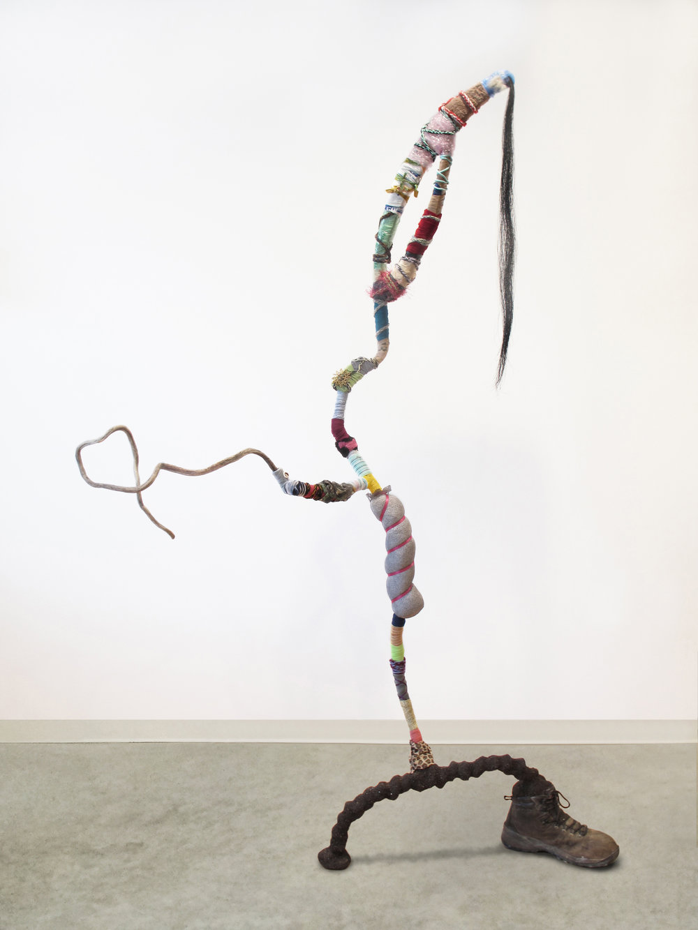 "Gina Herrera, A Salutation to All, Assorted found materials, 77 x 50 x 19 inches ""Reclaimed natural and man-made waste take on a humanoid shape, down to the wide-legged stance featuring an abandoned work boot. A twisting stick appendage extends in greeting, seeks acknowledgement."""
