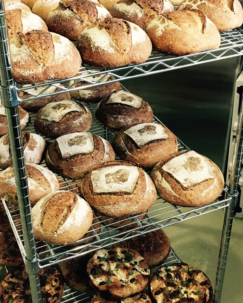 Origin Breads - ORIGIN Breads bakes small batches of naturally-leavened, long-fermented breads with Wisconsin-grown and stone-milled organic wheat and grains. We're proud to source our organic wheat, rye, spelt, buckwheat and corn locally from Lonesome Stone Milling in Lone Rock, Wisconsin. Thanks to Lonesome Stone's small community of local farmers, we can tell you the name of the farmer who grew the wheat for every bag of flour we use. ORIGIN Breads makes a variety of loaves, but for the Eastside Farmers' Market we'll be featuring our focaccia and flatbreads. Our naturally-leavened round focaccia has a moist, chewy crumb filled with irregular holes and bookended by a crispy, olive-oily crust. To make our flatbreads, we use a smaller portion of our focaccia dough and flatten it out so it resembles a pizza more than a loaf of bread. Seasonal and local toppings vary throughout the market season.Originbreads.com