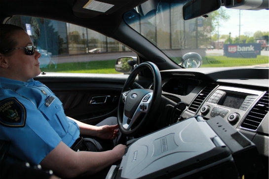 Officer Erika Estes in her police cruiser laden with lots of technology. STEPHANIE LECCI | ST. LOUIS PUBLIC RADIO
