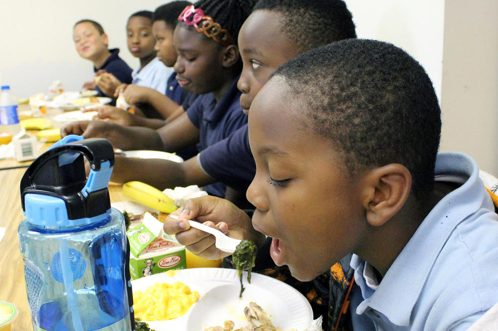 Every week at school, the students are exposed to new, healthy foods. Aron Williams is trying spinach. He will get a sticker rewarding him for being an adventurous eater. VERONIQUE LACAPRA | ST. LOUIS PUBLIC RADIO