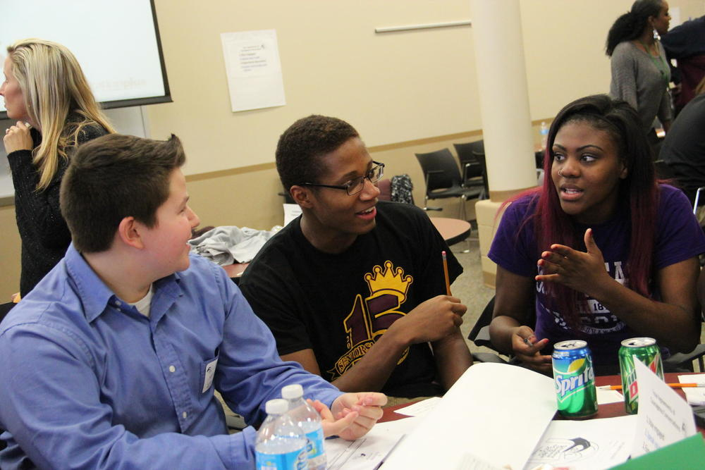 (From Left) Seckman Senior High School Kyle Edwards, Hazelwood East seniors Justin Mason and Teanna Bass pushed their tables together and created the idea for a student exchange program in the region. TIM LLOYD | ST. LOUIS PUBLIC RADIO
