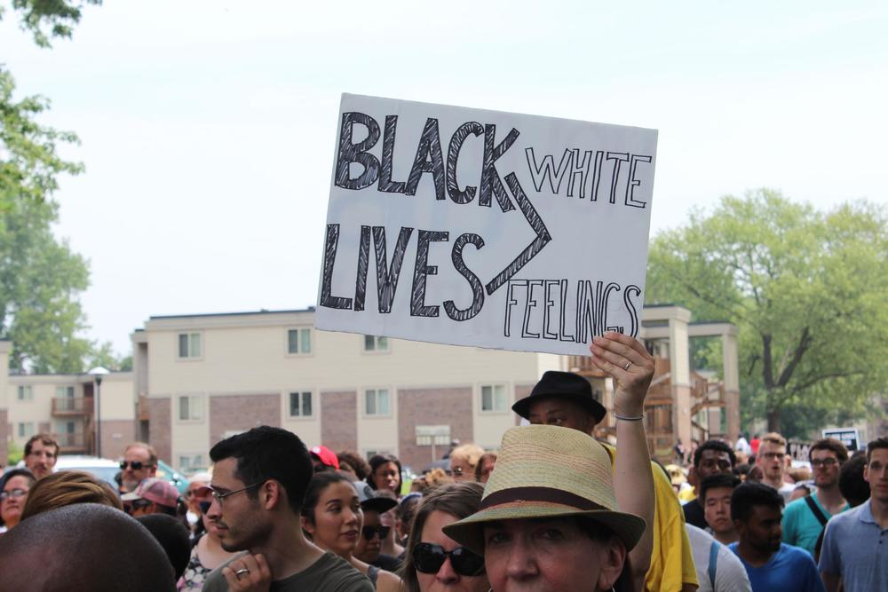 A demonstrator holds up a sign during a march to Greater St. Mark Church in Ferguson. JASON ROSENBAUM | ST. LOUIS PUBLIC RADIO