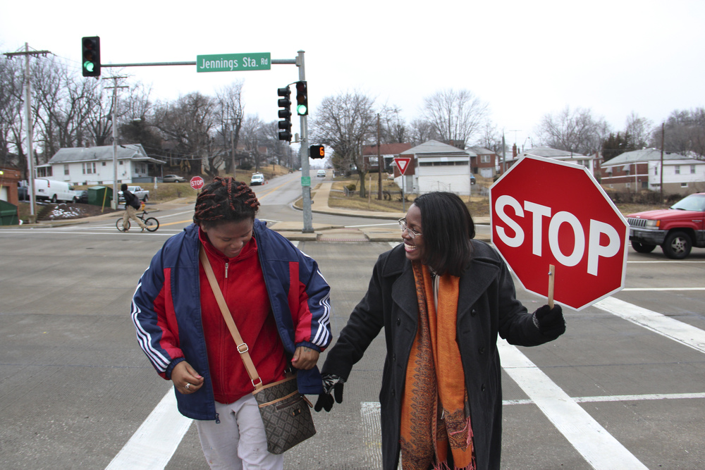Jennings Superintendent Tiffany Anderson takes her turn as a crossing guard, helping middle school student Courtney Abernathy across a busy intersection. Tim Lloyd, St. Louis Public Radio.