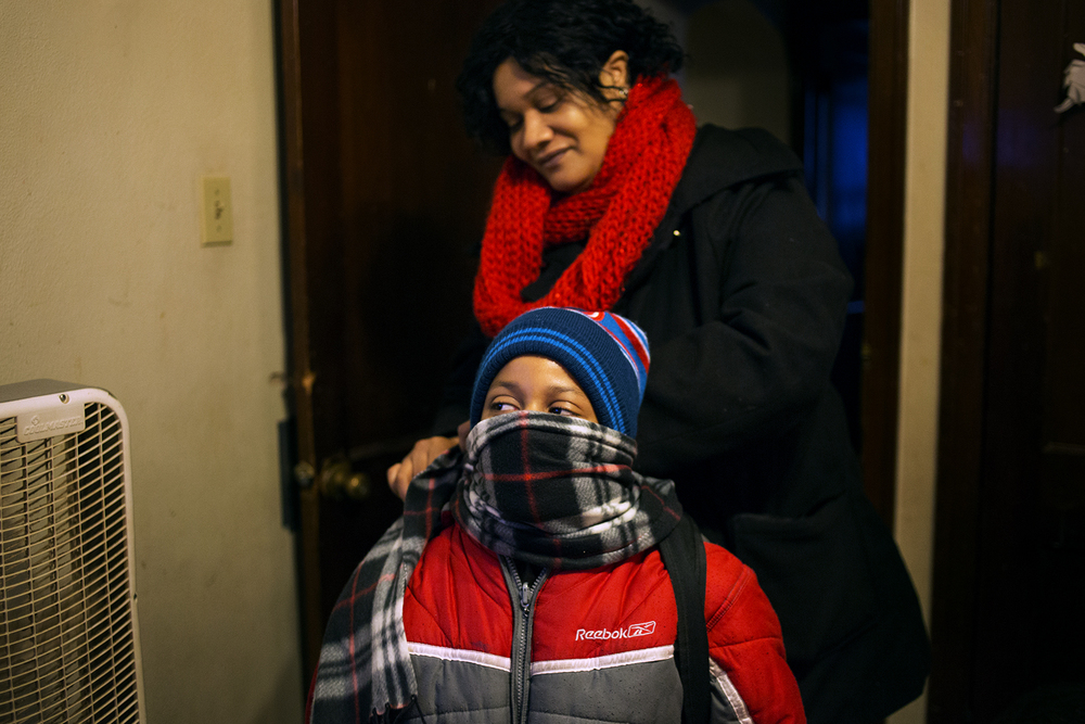 Keyanna Fields, helps her 8-year-old son Johnny with his scarf before their walk to the bus stop. Last year, when he was in first grade, Johnny spent about two months out of school because of suspensions. CAROLINA HIDALGO | ST. LOUIS PUBLIC RADIO