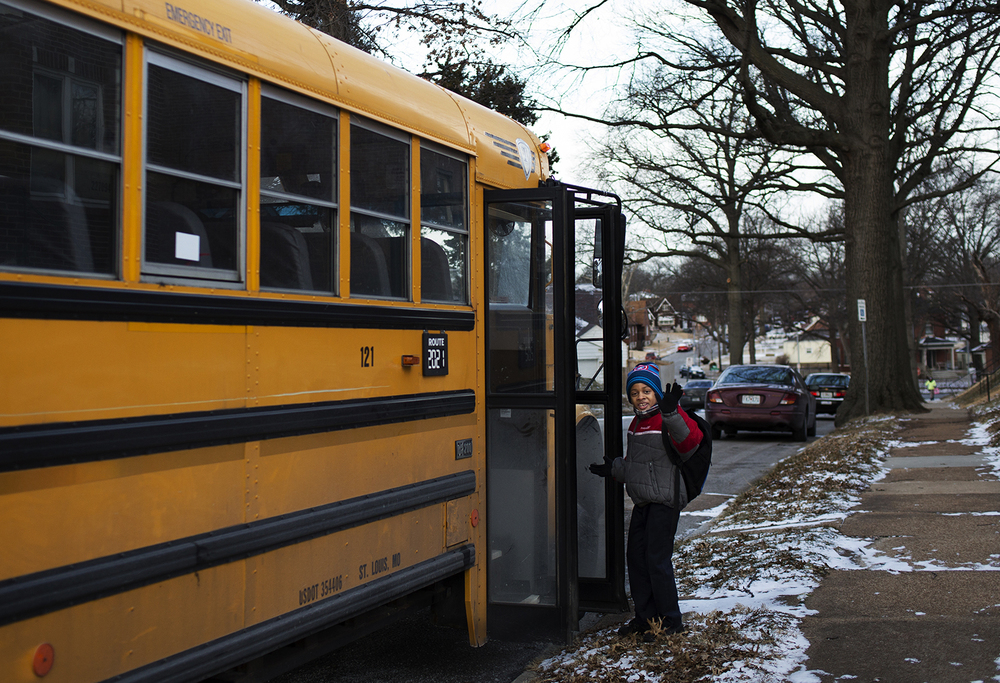 Johnny waves goodbye to his mom, Keyanna, as he boards the bus to school. CAROLINA HIDALGO | ST. LOUIS PUBLIC RADIO