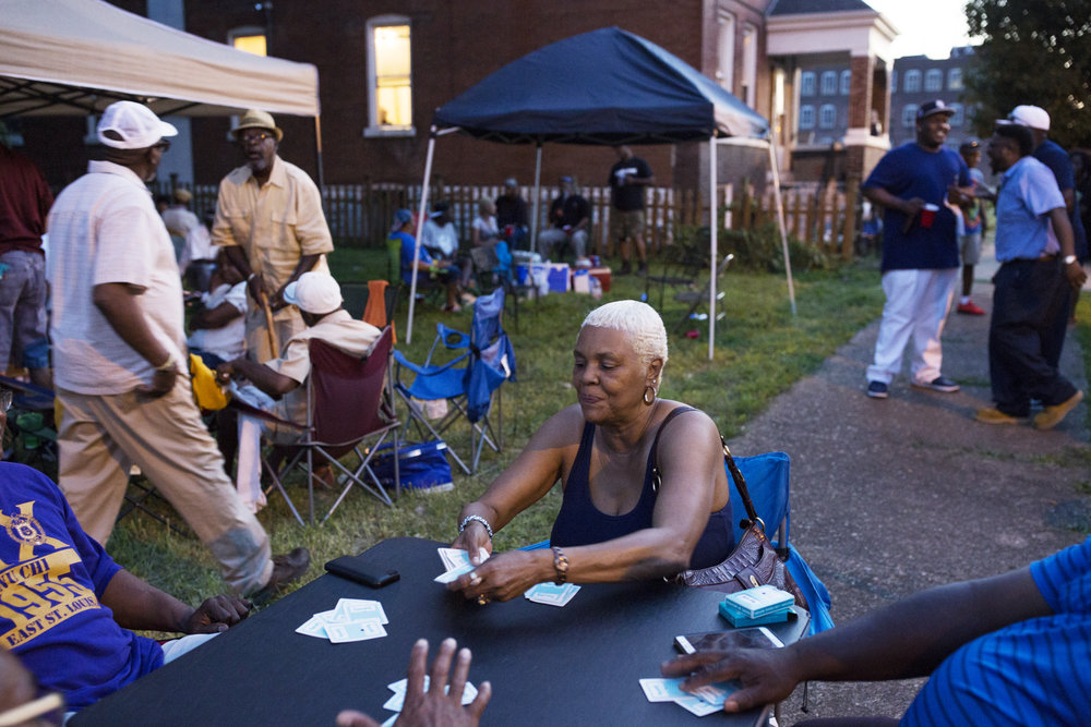 Brenda Nelson plays a card game with friends on Mullanphy Street during the street's last annual block party in July. CAROLINA HIDALGO | ST. LOUIS PUBLIC RADIO