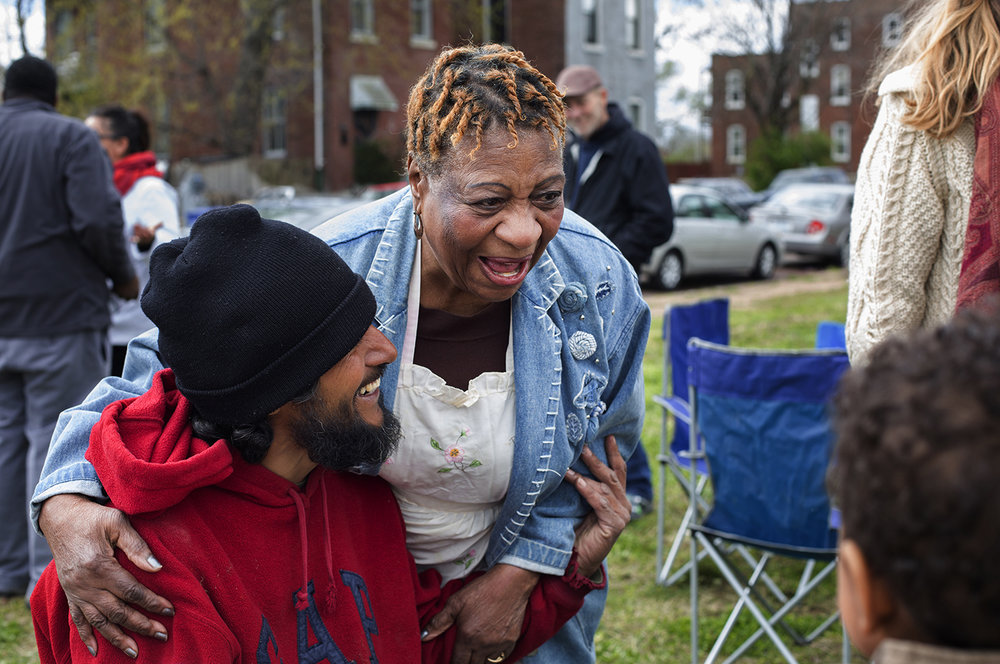 Ida Mobley and Gustavo Rendon, who live across the street from each other on Mullanphy Street, talk with neighbors and friends at a community picnic in April. CAROLINA HIDALGO | ST. LOUIS PUBLIC RADIO