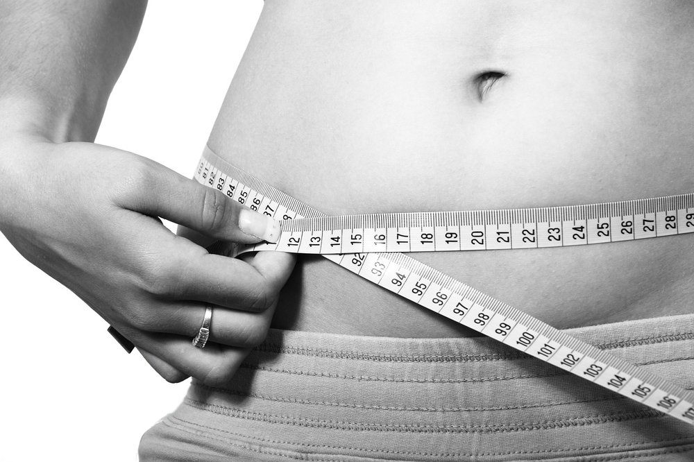woman with measuring tape around her abdomen fat shaming and illness shaming
