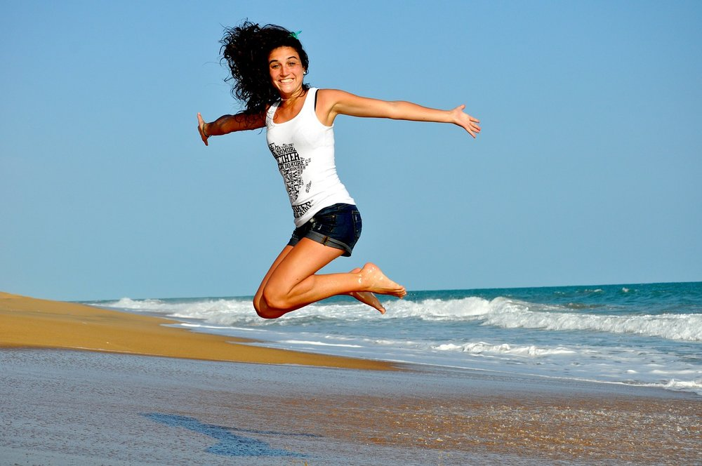 image of a healthy skinny white women jumping in the air with glee, full of vitality and health illness shaming