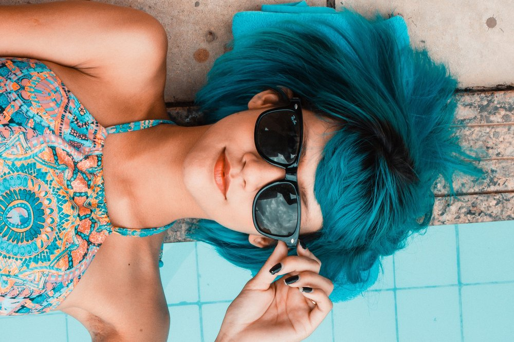 A blue haired woman, laying on her back on the pool decking, with short blue hair and sunglasses and a blue dress and black nail polish.