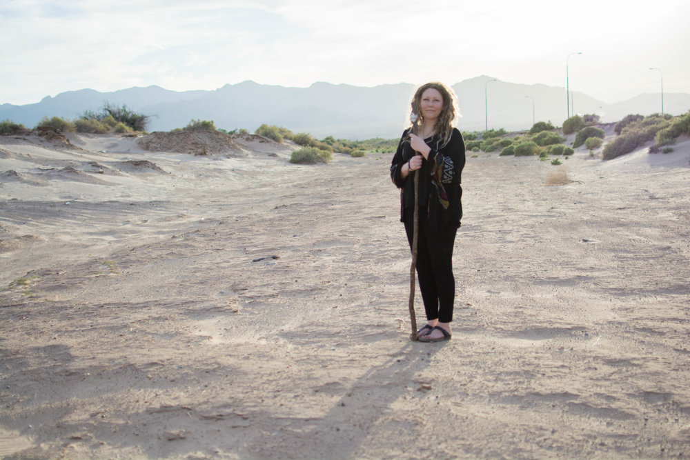 A photo of Kai Elliot.  She's wearing all black, and a black kimono, standing in the wide open desert, holding a walking stick.  It's sunny out, and the sun is bright behind her head.  You can see mountains in the background.