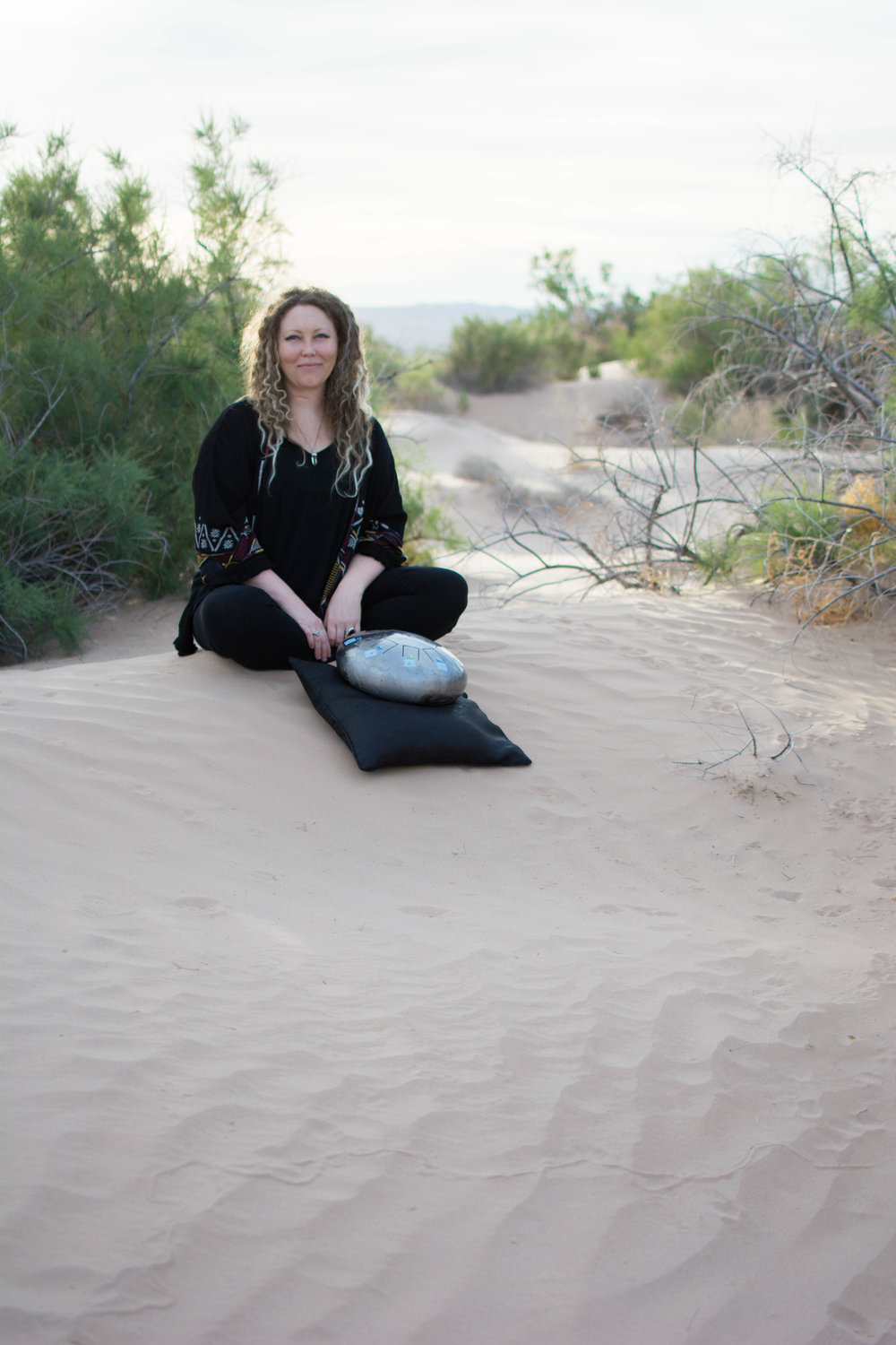 Kai Elliot sitting on a desert sand dune indian style.  She's wearing all black and has blonde and brown curly hair.  There are desert shrubs around her and ripples in the sand.  In front of her is a silver tank drum.