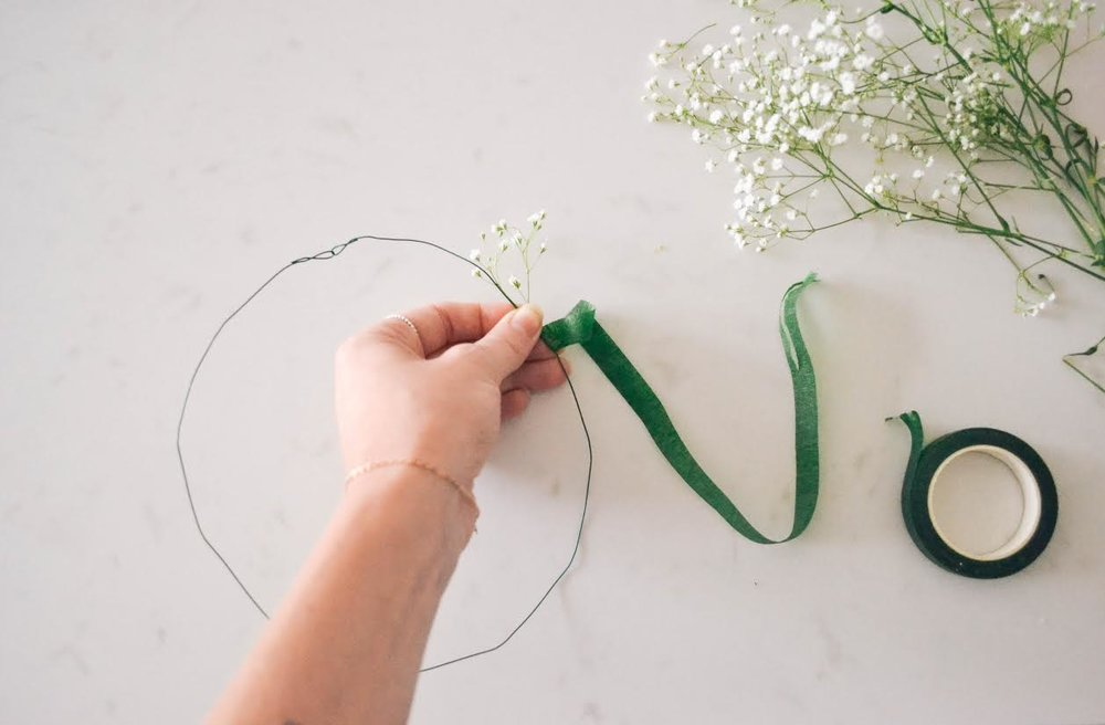 Start on one side of the wire as far down as you choose. Hold the snipped piece of flower alongside the wire and start wrapping the flower tape around it until it feels secure.