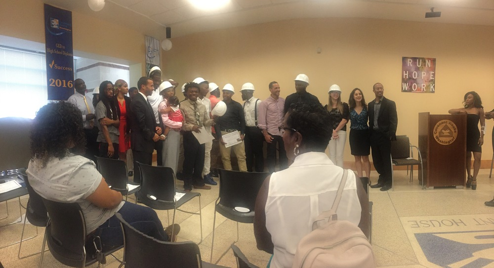 Graduates received hardhats, safety equipment and basic tools from James Harper of Hensel Phelps