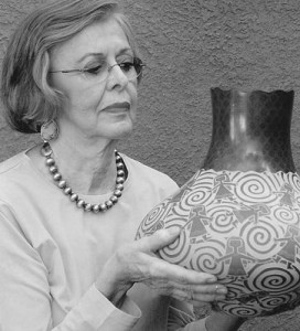 Marti, looking at a piece of pottery by Santa Clara artist Jody Naranjo