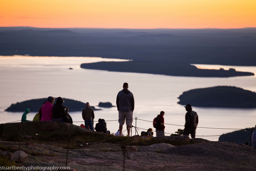 Sunrise on Cadillac mountain lights up the array of small islands below