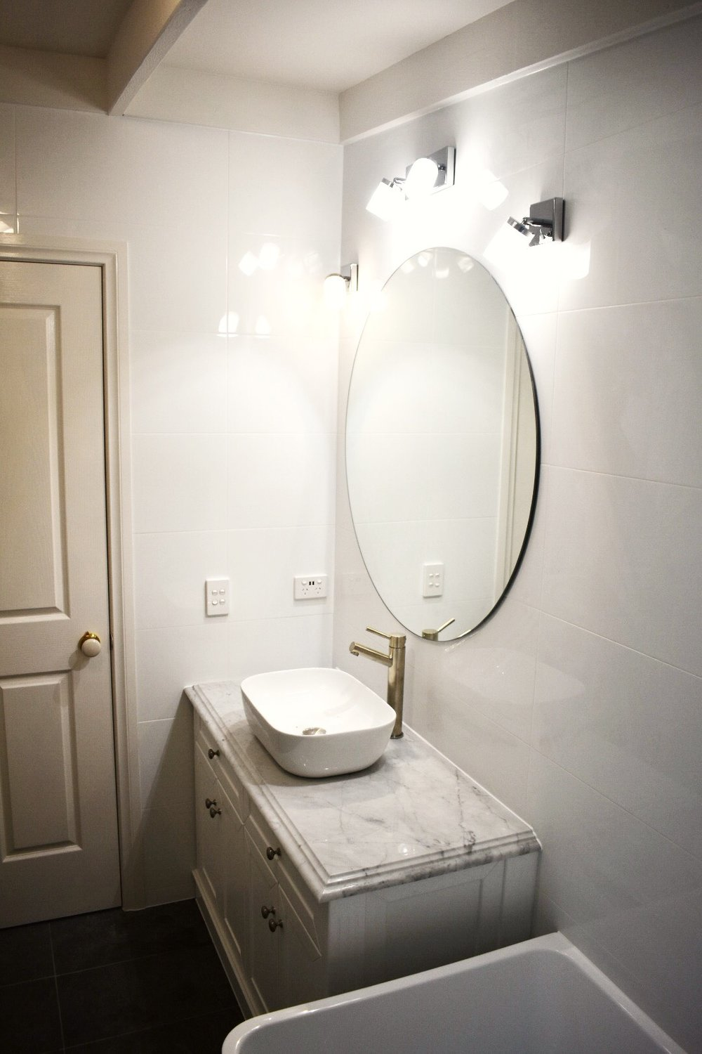 Bathroom renovation with mirrors and lighting