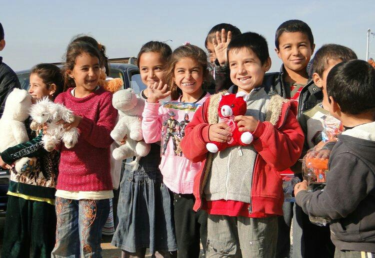Iraqi Yazidi children receiving stuffed animals from an international aid group. Credit: Wikimedia Commons