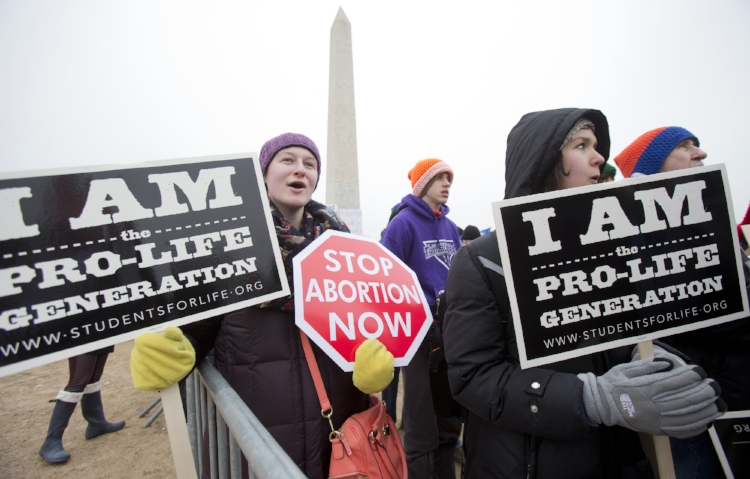 """In this Friday, Jan. 22, 2016, file photo, Michelle Doyle, left, joins the March for Life 2016 rally, commemorating the anniversary of 1973 """"Roe v. Wade"""" U.S. Supreme Court decision legalizing abortion in Washington. The annual rally will be held Friday, Jan. 27, 2017, on the National Mall in the nation's capital. (AP Photo/Manuel Balce Ceneta, File)"""