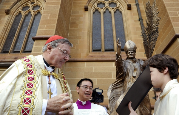 Photo: In this May 1, 2011 file photo, Cardinal George Pell, left, reads a bible during the blessing of a statue of John Paul ll at St Mary's Cathedral in Sydney, Australia. Australian police say they are charging Pell with historical sexual assault offenses. (AP Photo/Rob Griffith, File)