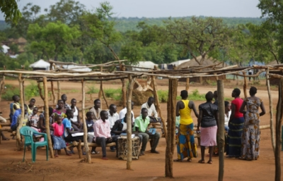 In this photo taken Sunday, June 4, 2017, the congregation sits under an open-air wooden frame as they attend a Sunday service at a pentecostal born-again church in Bidi Bidi refugee settlement in northern Uganda. The South Sudanese refugees meet in open-air churches rigged from timber with seats made only from planks of wood or logs drilled into the ground, yet these churches for the born-again Christians are oases of joy among the daily humiliations that come with rebuilding their lives. (AP Photo/Ben Curtis)