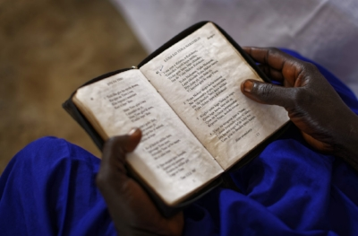 In this photo taken Sunday, June 4, 2017, a woman church leader reads from a Bible in her native Bari language, at the United Church which is held in a school classroom tent, in Bidi Bidi refugee settlement in northern Uganda. The South Sudanese refugees meet in open-air churches rigged from timber with seats made only from planks of wood or logs drilled into the ground, yet these churches for born-again Christians are oases of joy among the daily humiliations that come with rebuilding their lives. (AP Photo/Ben Curtis)