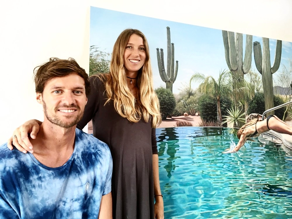 Isaac and Erika pictured in their Byron Bay home with one of Isaac's new paintings.