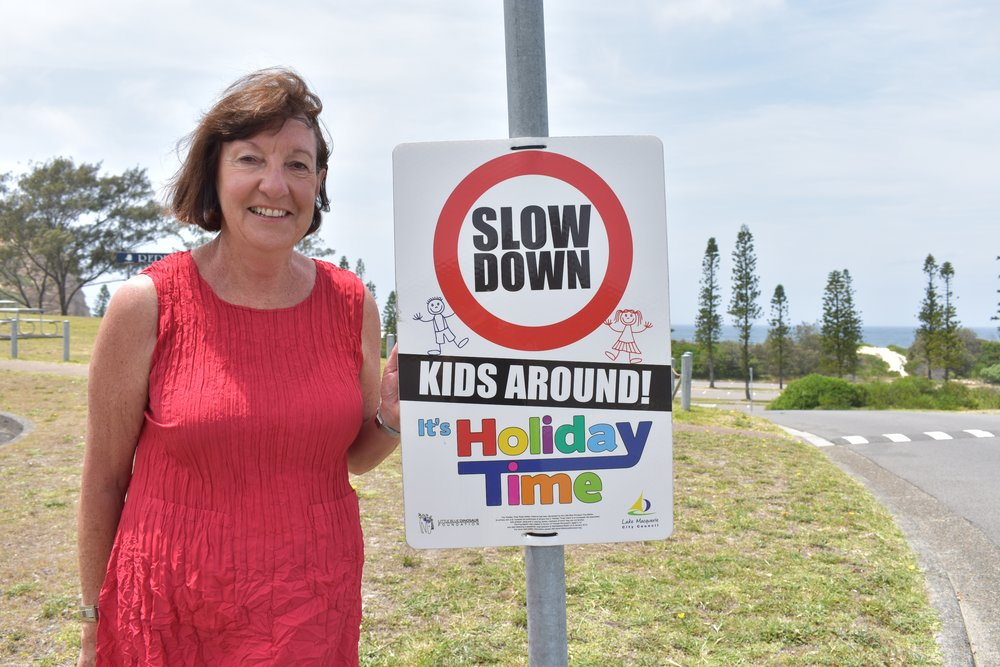 Picture:  Mayor of Lake Macquarie, Cr Kay Fraser, pictured with a Holiday Time sign at Redhead, urges drivers to slow down and help keep kids safe over the holiday season